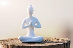 La siluetta di yoga di pratica della donna e medita su superficie di legno al tramonto Immagine Stock