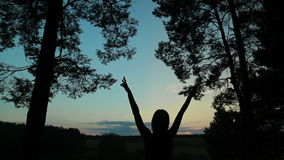 La siluetta felice della giovane donna contro il cielo solleva le mani su in aria video d archivio