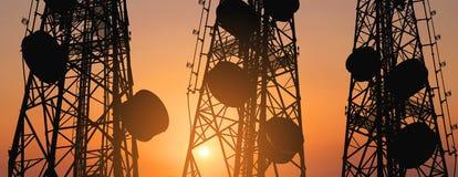 La siluetta, la telecomunicazione si eleva con le antenne della TV ed il riflettore parabolico nel tramonto, composizione in pano immagini stock
