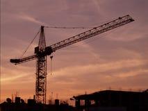La siluetta nera di alta gru e di una casa non finita sul cielo rosa di tramonto del fondo Fotografia Stock