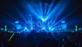 La siluetta in night-club nell'ambito dei raggi luminosi blu irradia Fotografia Stock Libera da Diritti