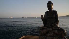 La siluetta parziale di Buddha di legno in acqua con il sole si svasa video d archivio