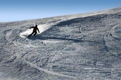 La siluetta retroilluminata dell'uomo in sci di pratica di azione che va veloce ed aggressivo giù nevica sport invernali del pend fotografia stock libera da diritti