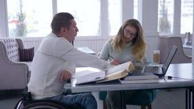 La singola istruzione per paralizzato, occhiali delle donne dell'istitutore tiene la lezione per gli uomini disabili sulla sedia  stock footage