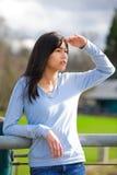 La situación adolescente joven de la muchacha, inclinándose contra la verja en el shading del parque observa para mirar apagado p Imagenes de archivo