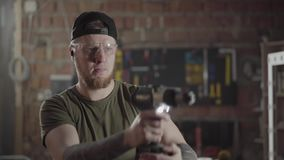 La situación barbuda del carpintero con destornillador de la llave del reductor de velocidad en el taller y jugar con la herramie metrajes