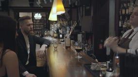 La situación confiada experimentada del camarero detrás de la barra de un restaurante costoso o de un pub hace un cóctel con una  metrajes