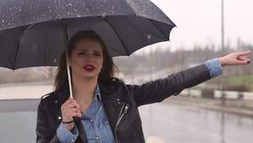 La situaci?n de la muchacha del trastorno debajo de un paraguas en el camino y coge el coche almacen de metraje de vídeo