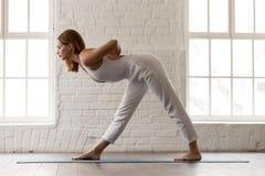 La situación de la mujer en la actitud de Parsvottanasana, una echada a un lado dobla ejercicio de la yoga foto de archivo