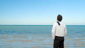 La situaci?n del hombre de negocios en la playa que mira al mar metrajes