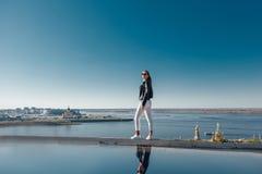 La situación elegante de la muchacha en una montaña, cielo azul reflejó en el agua fotos de archivo