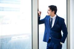La situación hermosa joven del hombre de negocios en la ventana imagen de archivo libre de regalías