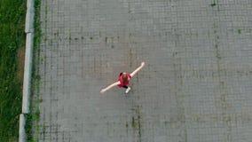 La situación inspirada hermosa joven de la bailarina de la mujer en el tejado y puso su cabeza y comienza a bailar metrajes