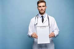 La situación masculina del doctor con la carpeta, doc. está llevando el uniforme blanco y un lazo, se coloca en un fondo azul cla imagen de archivo