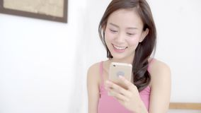 La situación sonriente de la mujer asiática joven hermosa del retrato que mira el teléfono móvil elegante que lee la red social c