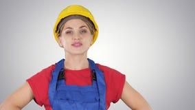 La situaci?n sonriente de la mujer del trabajador del constructor y las actitudes cambiantes doblan las manos, manos en caderas,  almacen de metraje de vídeo