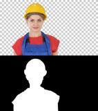 La situación sonriente de la mujer del trabajador del constructor y las actitudes cambiantes doblan las manos, manos en caderas,  foto de archivo libre de regalías