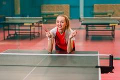 La situación sonriente del jugador de tenis en la tabla para los tenis de mesa foto de archivo