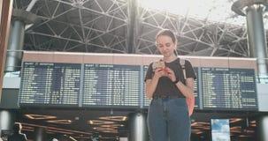 La situaci?n hermosa joven de la mujer en el aeropuerto escribe un mensaje almacen de metraje de vídeo