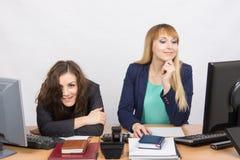 La situación en la oficina - miradas locas de una muchacha en la imagen, su colega que mira el monitor Fotos de archivo libres de regalías