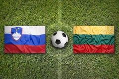 La Slovénie contre Drapeaux de la Lithuanie sur le terrain de football Photo stock