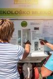 La Slovénie, Isola 29 août 2012 Une femme achète le lait dans la machine en vente de rue de lait Trayez dans des bouteilles et pu images stock