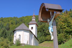 La SLOVENIA: Una chiesa tradizionale in colline di Skofja Loka con Jesus Christ su un incrocio nella priorità alta Fotografia Stock Libera da Diritti