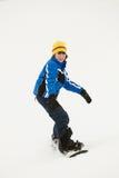 La snowboard joven del muchacho abajo se inclina el día de fiesta foto de archivo libre de regalías
