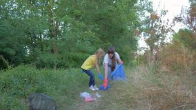 La société contre la pollution, peu de fille aide la femme à rassembler des ordures de plastique et de polyéthylène dans le momen banque de vidéos