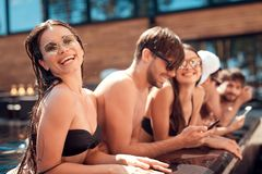 La société de jeunes amis regardent des photos prises sur le smartphone dans la piscine pendant l'été Photographie stock