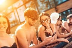 La société de jeunes amis regardent des photos prises sur le smartphone dans la piscine pendant l'été Photos stock