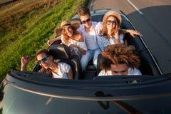 La société de jeunes filles heureuses et les types s'asseyent dans une route convertible noire de voiture un jour ensoleillé Vue  image stock