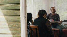 La société des amis détendent à la table sur la terrasse de la maison de campagne Guitare de jeu d'homme banque de vidéos