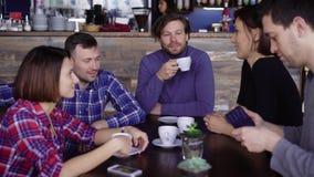 La société des amis d'une cinquantaine d'années communiquent dans un petit restaurant, où ils ont commandé le dîner sur le menu D banque de vidéos