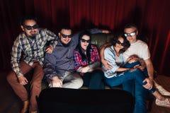 La société des jeunes heureux regardent la TV à la maison Image stock