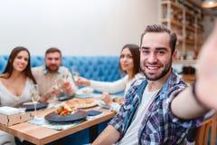 La société des jeunes s'assied dans un café, le type fait un selfie Photographie stock libre de droits