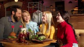 La société gaie des amis a un repos dans un déjeuner en café, ils mangent des hamburgers clips vidéos