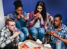 La société, les amis noirs et blancs mangent de la pizza à la maison Photo stock