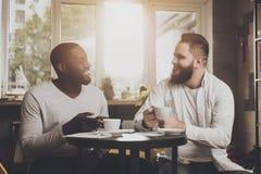 La société multi-ethnique des hommes communique dans un café photo stock