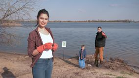 La sociedad joven contra la contaminación, retrato del voluntario sonriente de la mujer da el pulgar para arriba en el fondo unfo metrajes