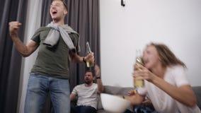 La società caucasica di giovani amici guarda la partita sulla TV con interesse, esperienza ed esprime le loro emozioni brillantem video d archivio