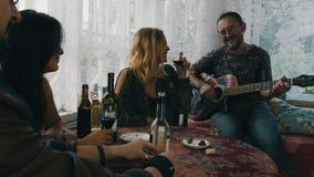La società degli amici beve l'alcool sul terrazzo in casa di campagna Chitarra del gioco dell'uomo archivi video