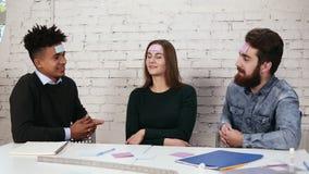 La società degli amici divertendosi nell'ufficio Pezzi di carta dei giovani incollati sulle parole di congettura e della fronte video d archivio