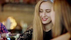 La società dei giovani è chiacchierante e bevente i coctails nella barra stock footage