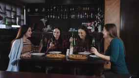 La società delle ragazze allegre nella pizzeria Amica in pizzeria che beve birra e che mangia pizza, chiacchierante e video d archivio