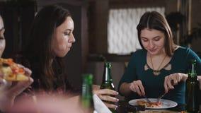 La società delle ragazze allegre nella pizzeria Amica in pizzeria che beve birra e che mangia pizza, chiacchierante e stock footage