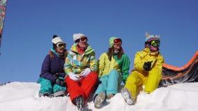 La società delle ragazze intelligenti si siede su neve e allegramente parla stock footage