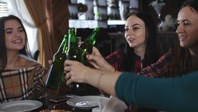 La società di belle ragazze nelle bottiglie tintinnanti della pizzeria di birra stock footage