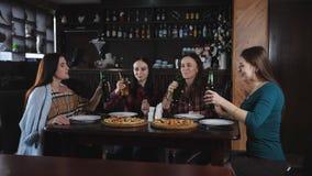 La società di belle ragazze nelle bottiglie tintinnanti della pizzeria di birra archivi video