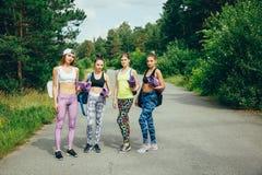 La società di giovani amici attraenti delle donne con articolo sportivo che va per un allenamento nel parco Fotografie Stock Libere da Diritti